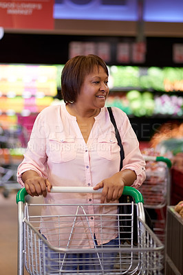 Buy stock photo Shot of a mature woman pushing a shopping cart in a grocery store