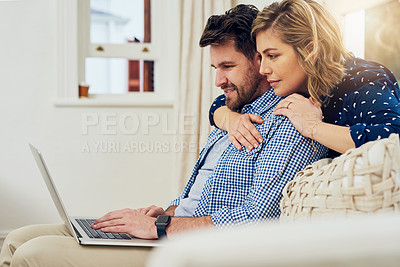 Buy stock photo Shot of an attractive couple using a laptop together at home