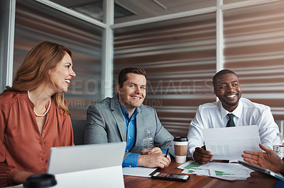 Buy stock photo Portrait of a businessman sitting alongside his colleagues during a meeting in an office