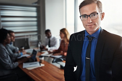 Buy stock photo Portrait of a confident businessman standing in an office with his colleagues in the background