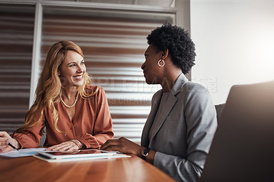 Buy stock photo Shot of two businesswomen going through paperwork in an office
