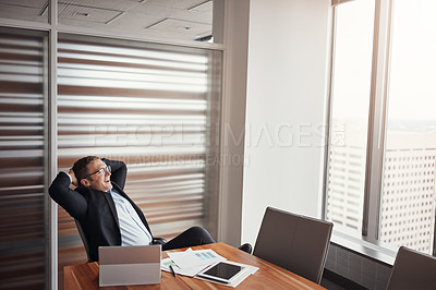 Buy stock photo High angle shot of a handsome businessman sitting with his hands behind his head in his corporate office