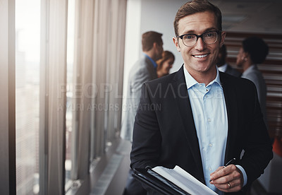 Buy stock photo Portrait of a professional businessman standing in an office with colleagues in the background
