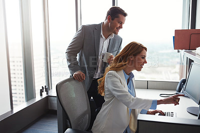 Buy stock photo Cropped shot of man standing behind a woman as she works on her computer