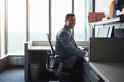 Buy stock photo Shot of a businessman working on his computer at his desk