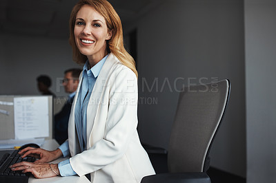 Buy stock photo Shot of a businesswoman sitting at her desk with colleagues in the background