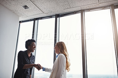 Buy stock photo Low angle shot of two corporate businesswomen shaking hands during a meeting in the boardroom