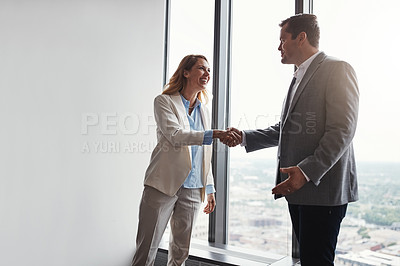 Buy stock photo Low angle shot of two corporate businesspeople shaking hands during a meeting in the boardroom