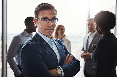 Buy stock photo Cropped portrait of a handsome businessman standing with his arms folded during a meeting in the boardroom