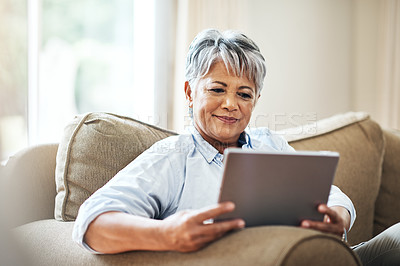 Buy stock photo Shot of a senior woman using a tablet at home