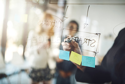 Buy stock photo Cropped shot of three businesswoman using a glass wipe board during a brainstorming session