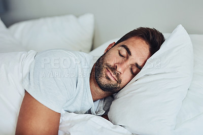Buy stock photo Shot of a tired young man sleeping comfortably in his bed without a sign of being disturbed