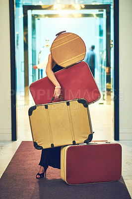 Buy stock photo Shot of an unrecognizable young woman carrying a whole bunch of luggage while trying to walk down the lobby of a hotel