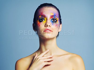 Buy stock photo Studio shot of an attractive young woman with brightly colored makeup against a blue background