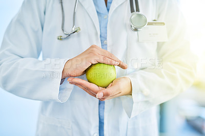 Buy stock photo Closeup shot of an unidentifiable doctor holding an apple in her hands