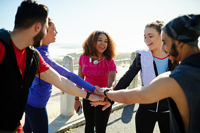 Buy stock photo Shot of a group of young cheerful friends forming a huddle before a fitness exercise outside during the day
