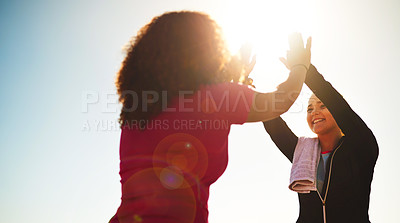 Buy stock photo Low angle shot of two cheerful young friends exchanging high fives outside during the day