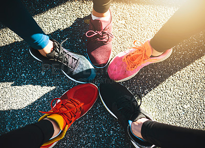 Buy stock photo Shot of a group of unrecognizable people's runnings shoes put next to each other in a circle outside during the day