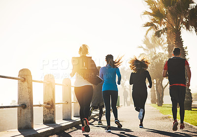 Buy stock photo Rearview shot of a fitness group out running on the promenade