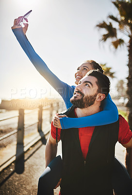 Buy stock photo Shot of a woman taking a selfie while out for a run with her boyfriend