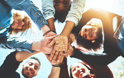 Buy stock photo High angle portrait of a diverse group of college friends standing outside with their hands in a huddle