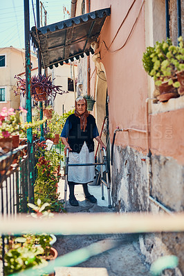 Buy stock photo Portrait of a senior woman standing on her front porch in an ancient city