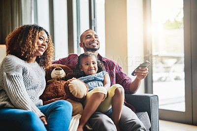 Buy stock photo Shot of a happy young family of three watching tv from the sofa at home