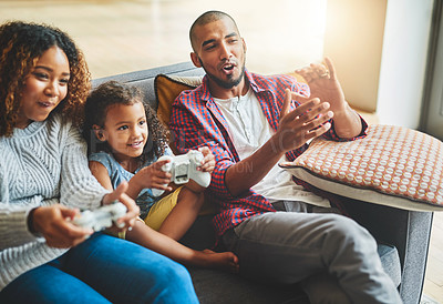 Buy stock photo Shot of an adorable little girl and her parents playing video games together on the sofa at home