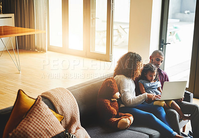 Buy stock photo Shot of an adorable little girl and her parents using a laptop together on the sofa at home