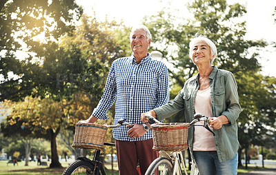Buy stock photo Shot of a senior couple going for a bicycle ride in the park
