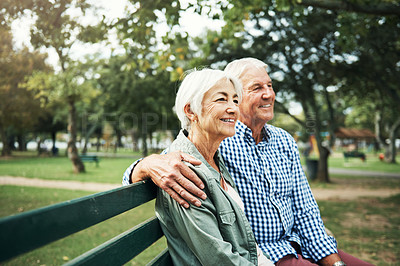 Buy stock photo Shot of a happy senior couple relaxing together on a park bench