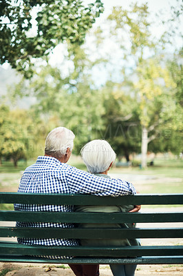 Buy stock photo Rearview shot of a senior couple relaxing together on a park bench
