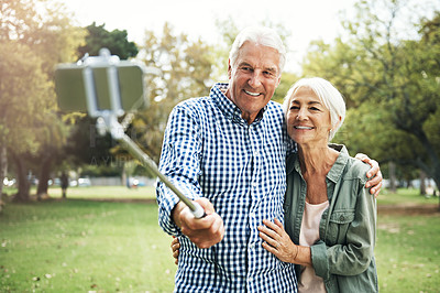 Buy stock photo Shot of a happy senior couple taking selfies with a selfie stick in the park