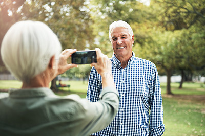 Buy stock photo Shot of a senior woman taking photographs of her husband on a mobile phone in the park