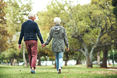 Buy stock photo Rearview shot of a mature couple walking hand in hand through the park