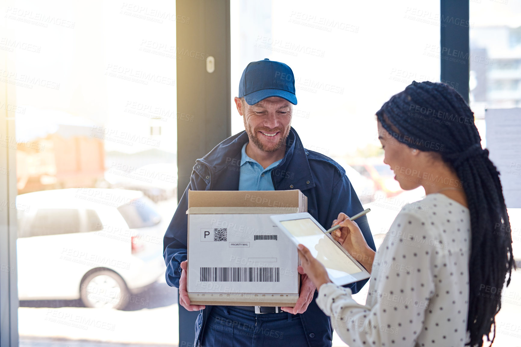 Buy stock photo Cropped shot of a handsome delivery man getting a signature from a female customer for her order