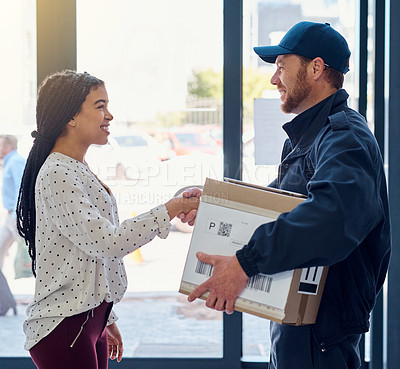 Buy stock photo Cropped shot of a handsome delivery man shaking hands with a female customer