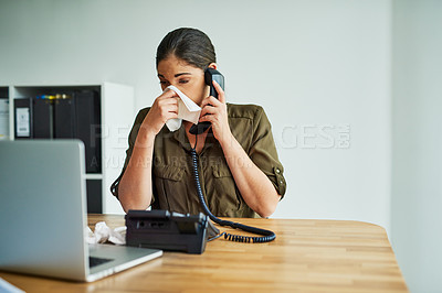 Buy stock photo Shot of a young businesswoman blowing her nose while speaking on a phone in an office