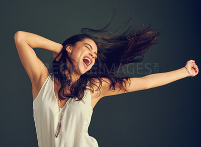 Buy stock photo Studio shot of a carefree young woman shouting with her arms raised and her hair blowing against a dark background