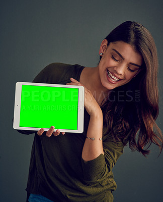 Buy stock photo Studio shot of an cheerful young woman holding a digital tablet while standing against a dark background