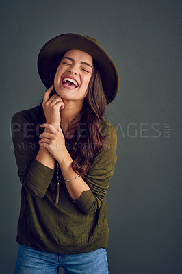 Buy stock photo Studio shot of a carefree young woman posing with a hat while standing against a dark background