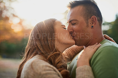 Buy stock photo Shot of an affectionate young couple spending a day outdoors
