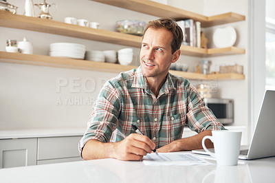 Buy stock photo Shot of a mature man writing notes while using a laptop at home