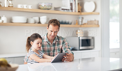Buy stock photo Shot of a father and his little daughter using a digital tablet together at home