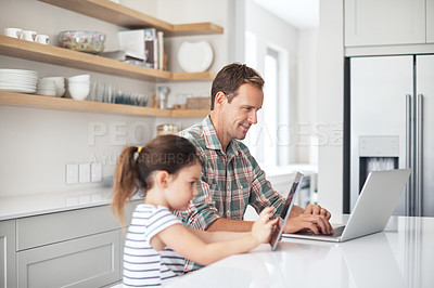 Buy stock photo Shot of a father and his little daughter using wireless technology at home