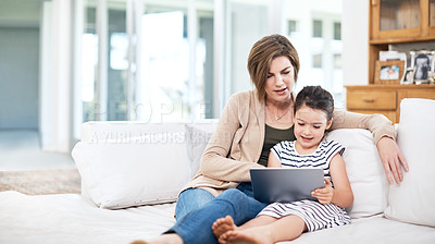 Buy stock photo Shot of a mother and her little daughter using a digital tablet at home