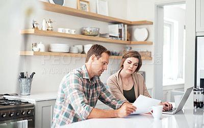 Buy stock photo Shot of a couple using a laptop while going through paperwork together at home