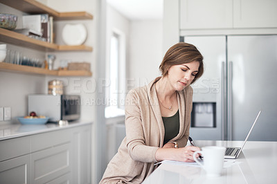 Buy stock photo Shot of a mature woman writing notes while using a laptop at home