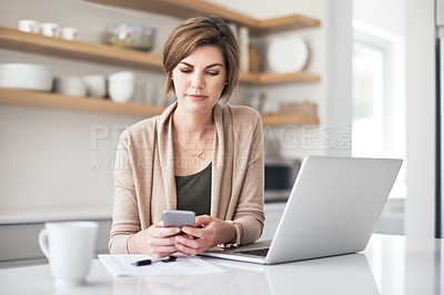 Buy stock photo Shot of a mature woman using a cellphone and laptop at home
