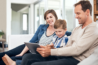 Buy stock photo Cropped shot of a young family of three using a tablet while sitting on their sofa at home